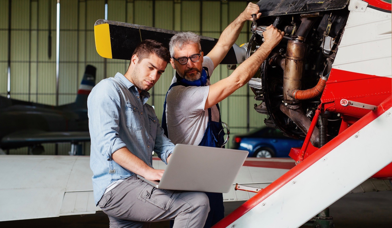 Engineer looking at laptop for maintenance an airplane.