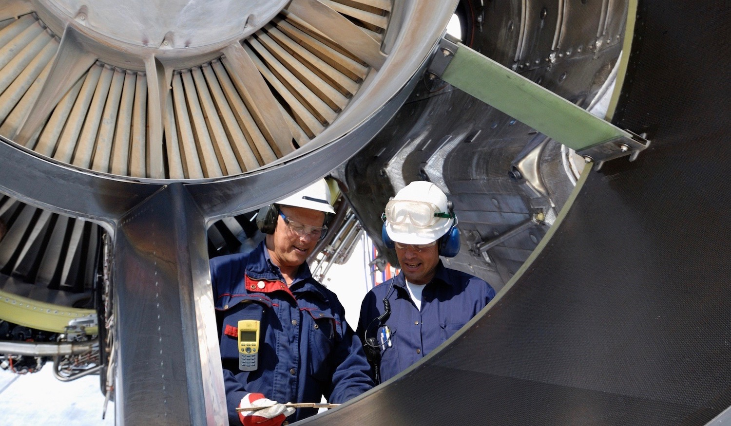 two male airplane technicians inside large jet engine