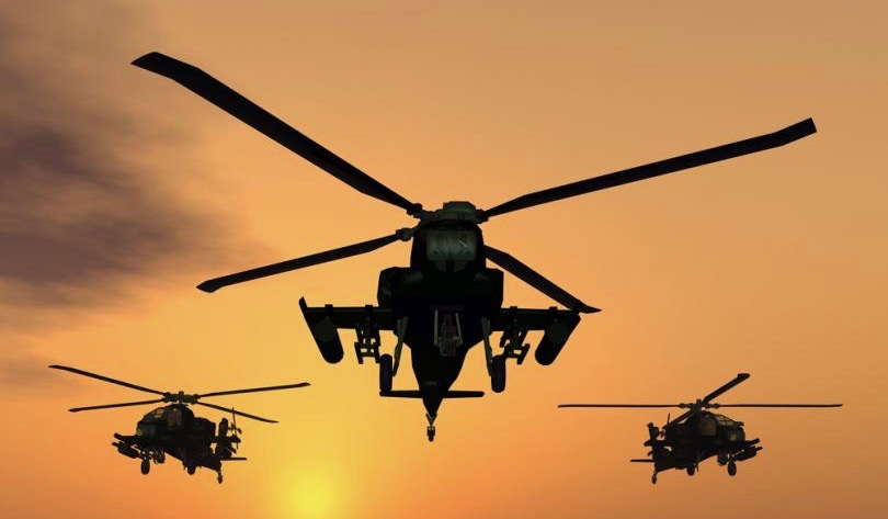 Rotary wing military plane in the sky during a sunset