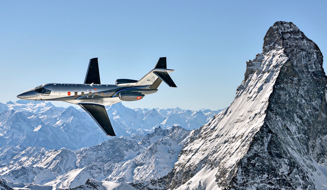 Pilatus aircraft flying around a snowy mountain