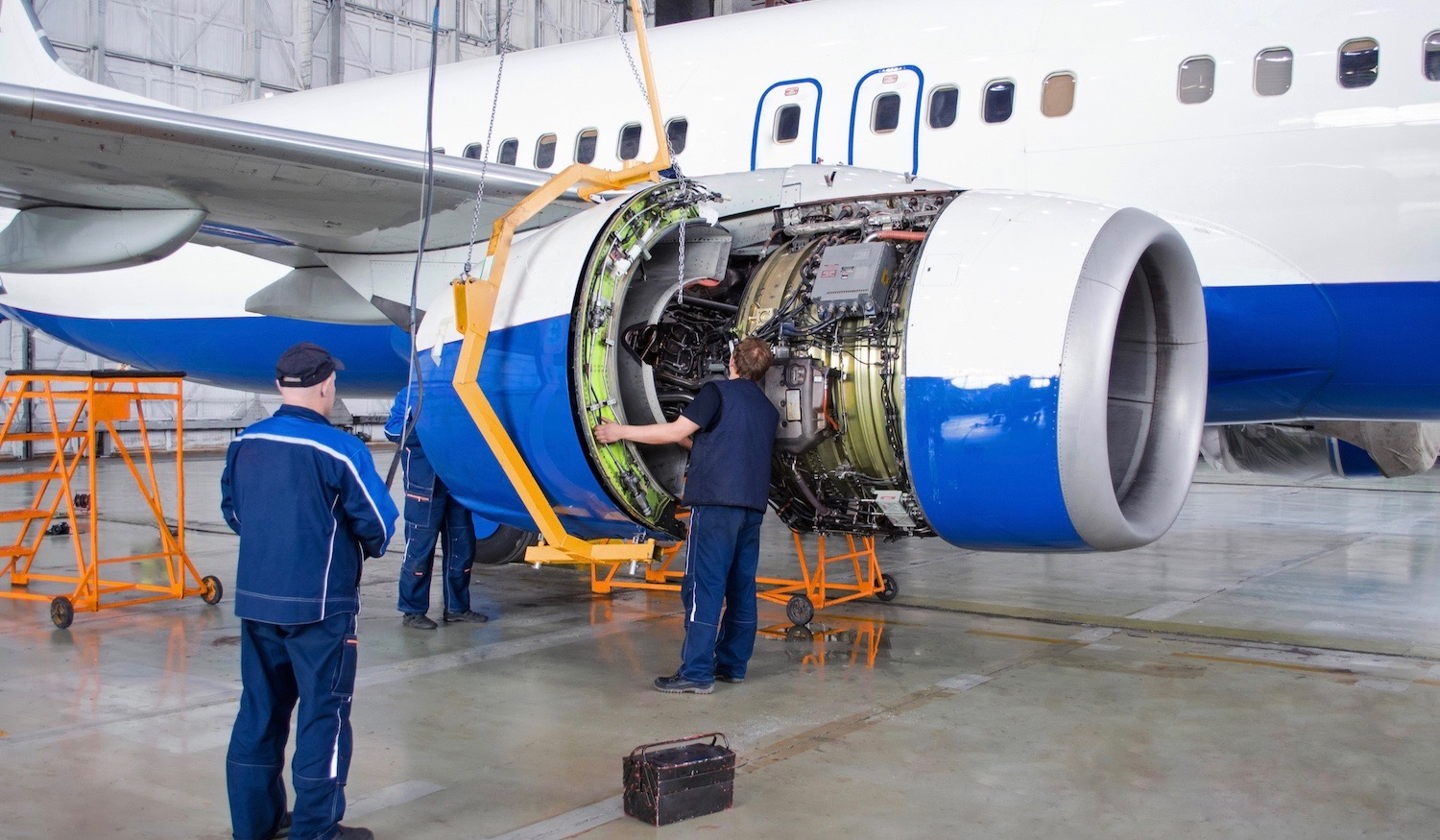 two men fixing jet engine in hanger wearing blue uniform