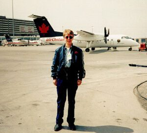 Dena Standing on aircraft runway in front of an Air Canada plane
