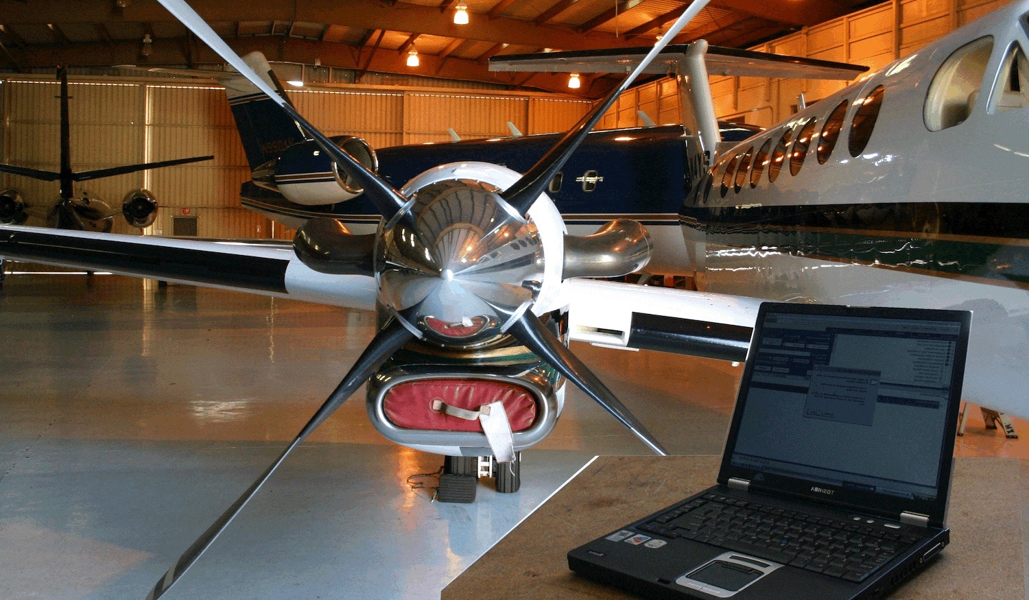 laptop on wooden desk in hanger with airplane in background