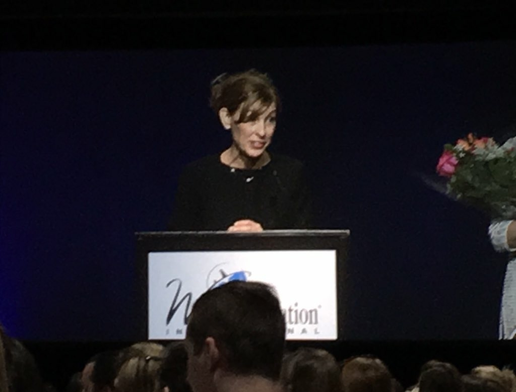 woman at podium speaking at conference