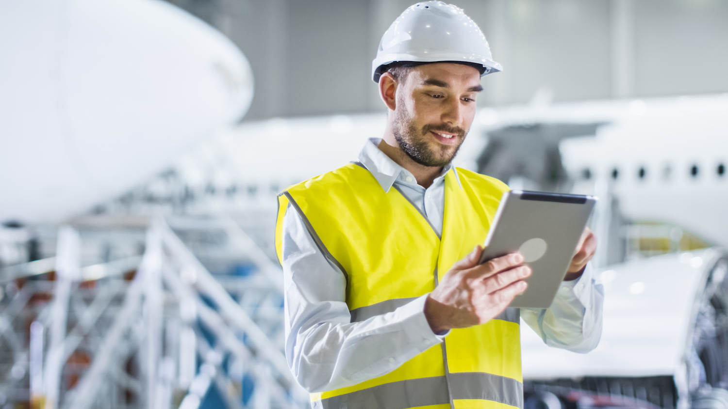 man in hard hat wearing yellow vest looking at tablet