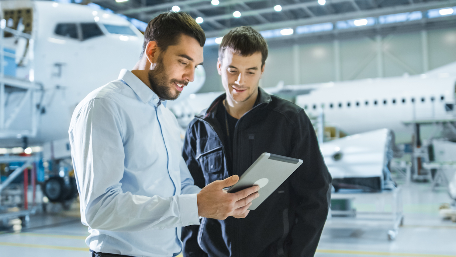 two male technicians on tablet in front of airplane