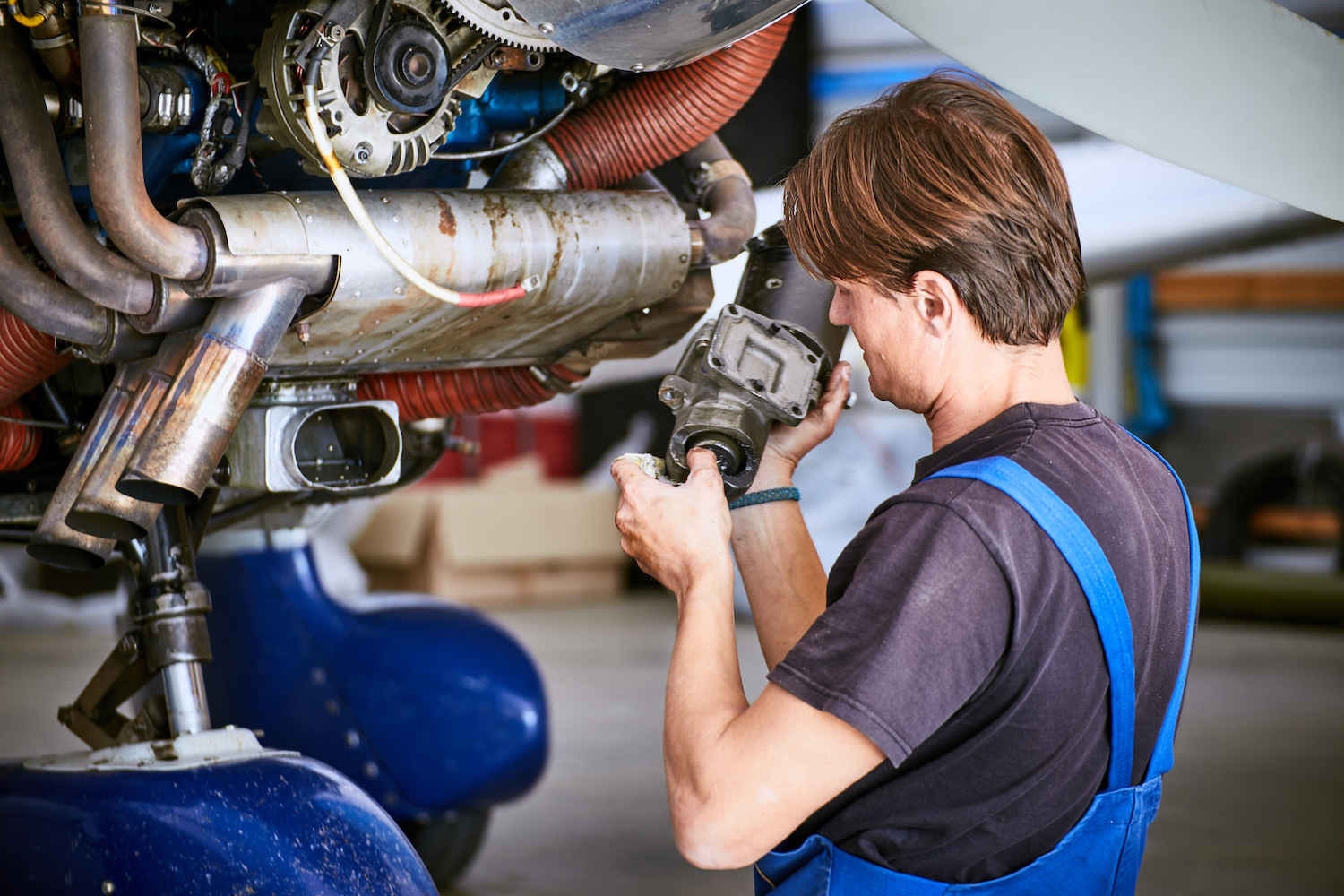 Removal and repair of an engine starter of an airplane by a service worker.
