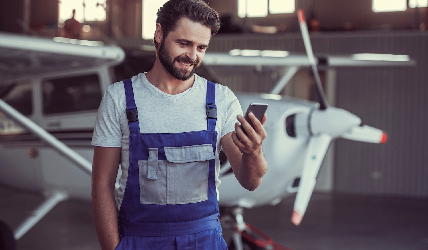 bearded mechanic in uniform is using a smart phone and smiling while standing near an aircraft in hangar